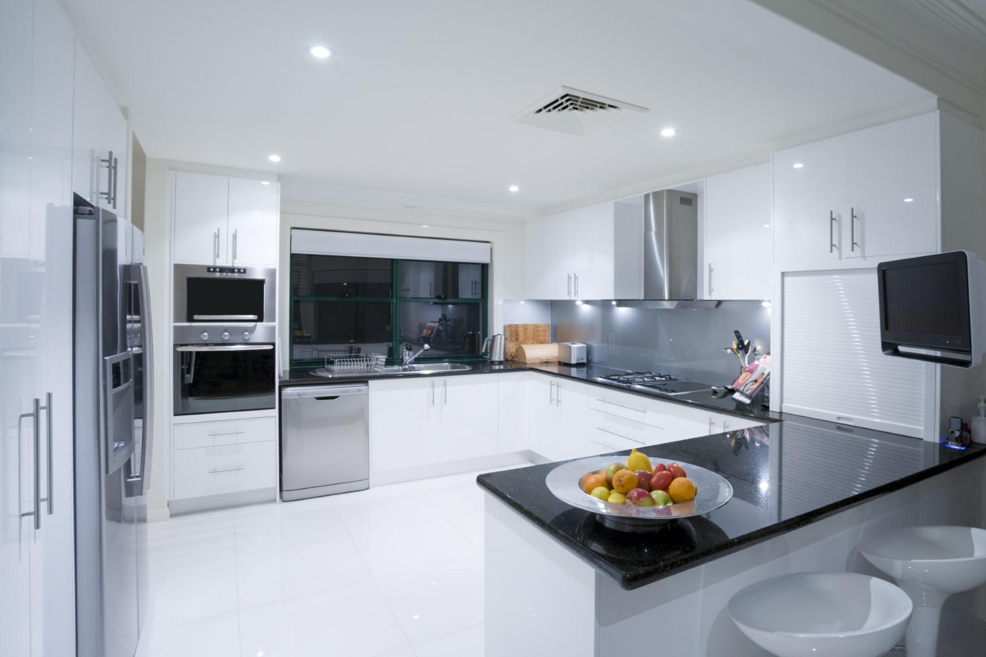 A modern kitchen with high gloss white cabinets, glossy black marble counter tops, glossy white tile floors, and stainless steel appliances. There is a bowl of fruit on the counter.