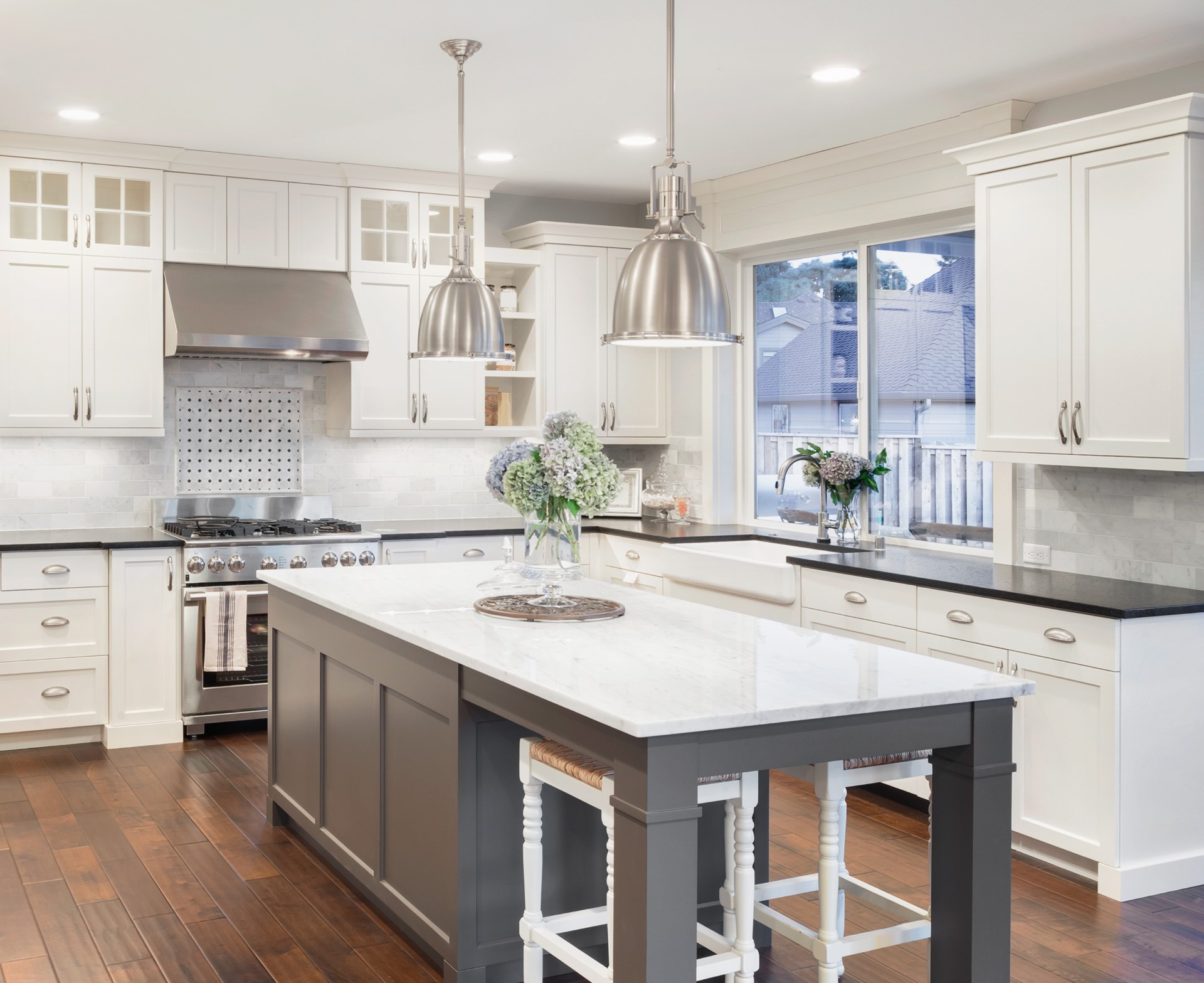 This french style contempory kitchen takes things to the next level. It starts with bright white cabinets to help open up the room. This cabinet style is gaining traction because it's a reasonably priced solution to updating your current outdated cabinets. I personally like having a dark colored island because it concentrates your focus on the beauty of the the cabinetry. Our