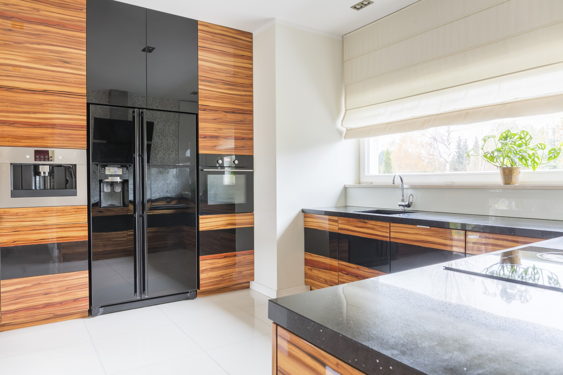Nothing displays elegance quite like out of the ordinary in this burned stained wood theme. This kitchen emphasizes on the glossy ebony tones that help bring out the fine grain in the burnt wood cabinets. This high level gloss is not the cheapest style, but it gives that surreal, abstract, nature type of feel.