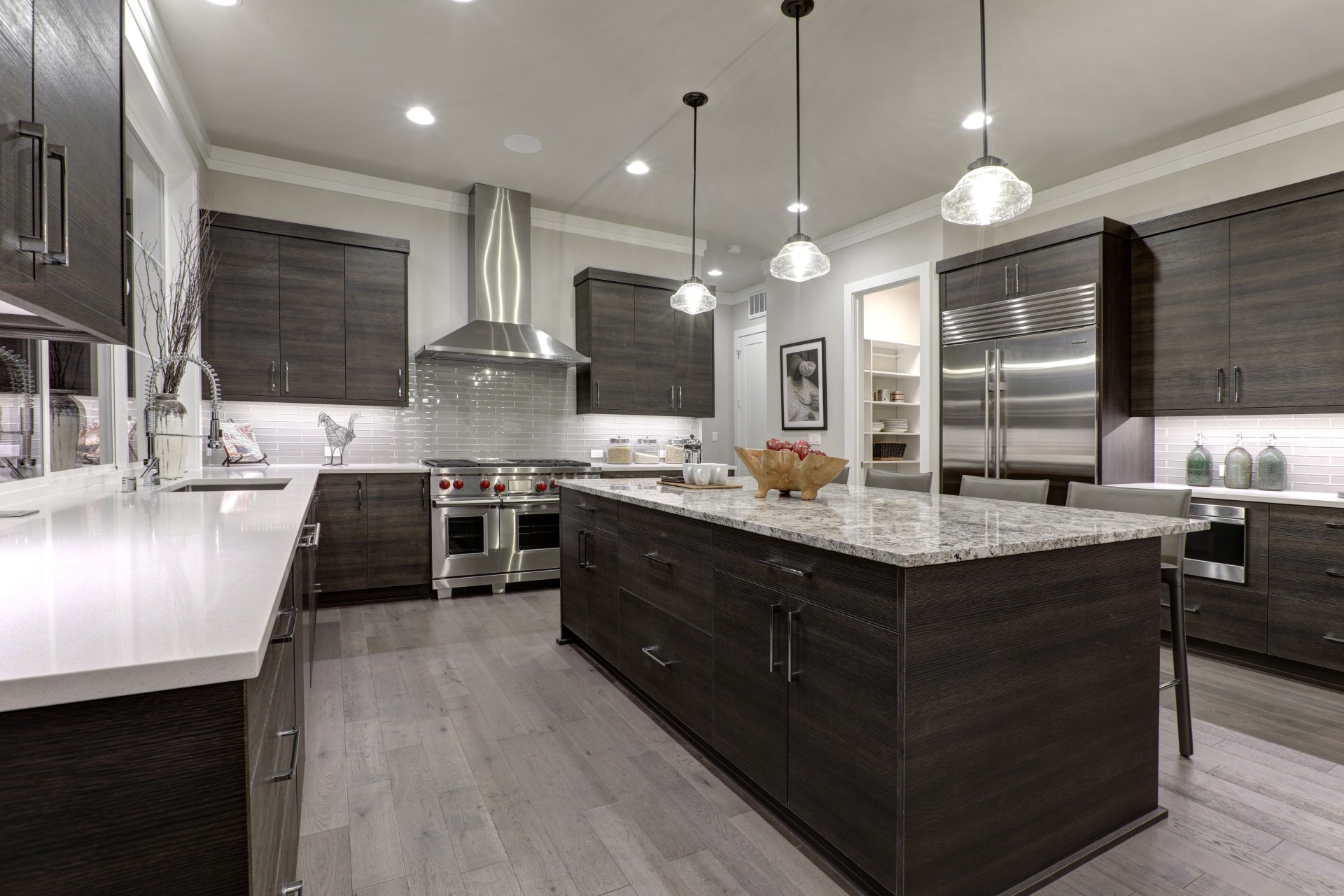 I kitchen with dark cabinets helps bring forth the beauty of your light flooring. A kitchen needs contrast and physique to achieve harmony in this modern style. When you mix wood, stone, and the bright sheen of stainless steel, it helps achieve the diversity that makes this style pop!