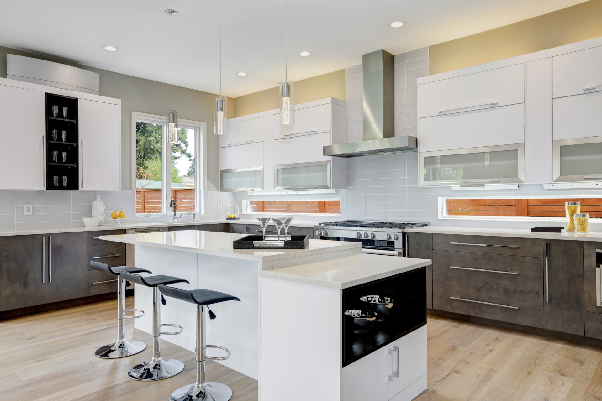 Adding champagne pendant lights is a clean way to polish out your kitchen. There are probably one of the most universal light fixtures that is bound to fit within any style. This contemporary kitchen is especially unique because of the see-through backsplash under the countertops which helps provide a spacious atmosphere.