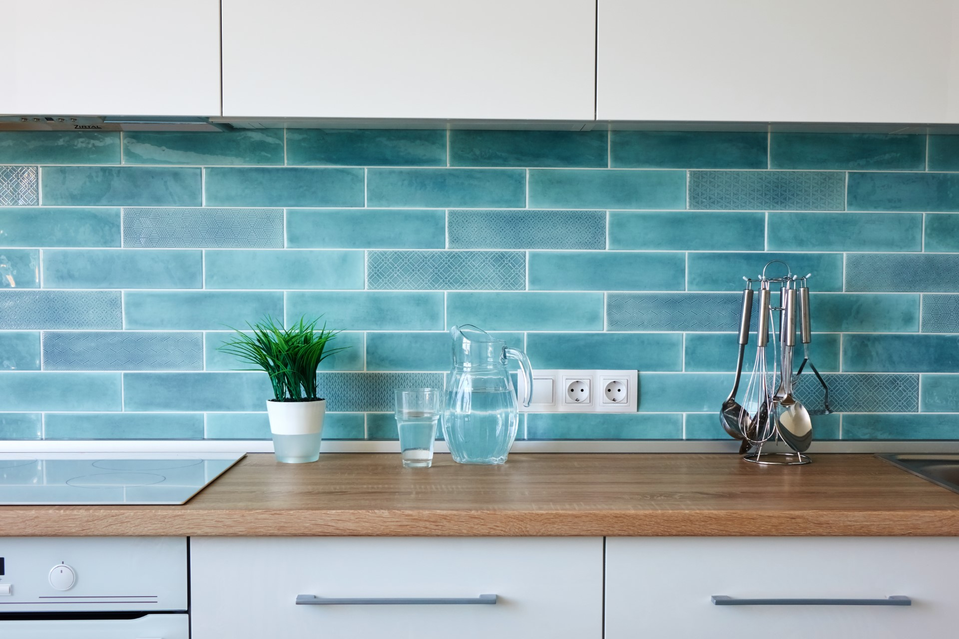 A blue backsplash coupled with a natural wood slab for a countertop is a different design that helps distinguish your kitchen from others.