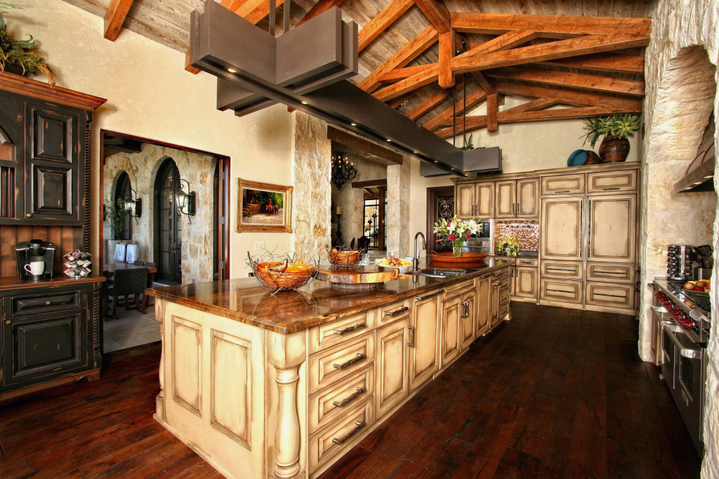 If you're going for more of an English farmhouse type of design, this can commonly be done if you remove the existing drywall and ran more decorative stained wood beams on the ceiling. This kitchen design idea is for the luxurious dream kitchen. It provides more than enough storage to organize to your hearts content with an extended island countertop with lighting and dark stained wood against light countertops.