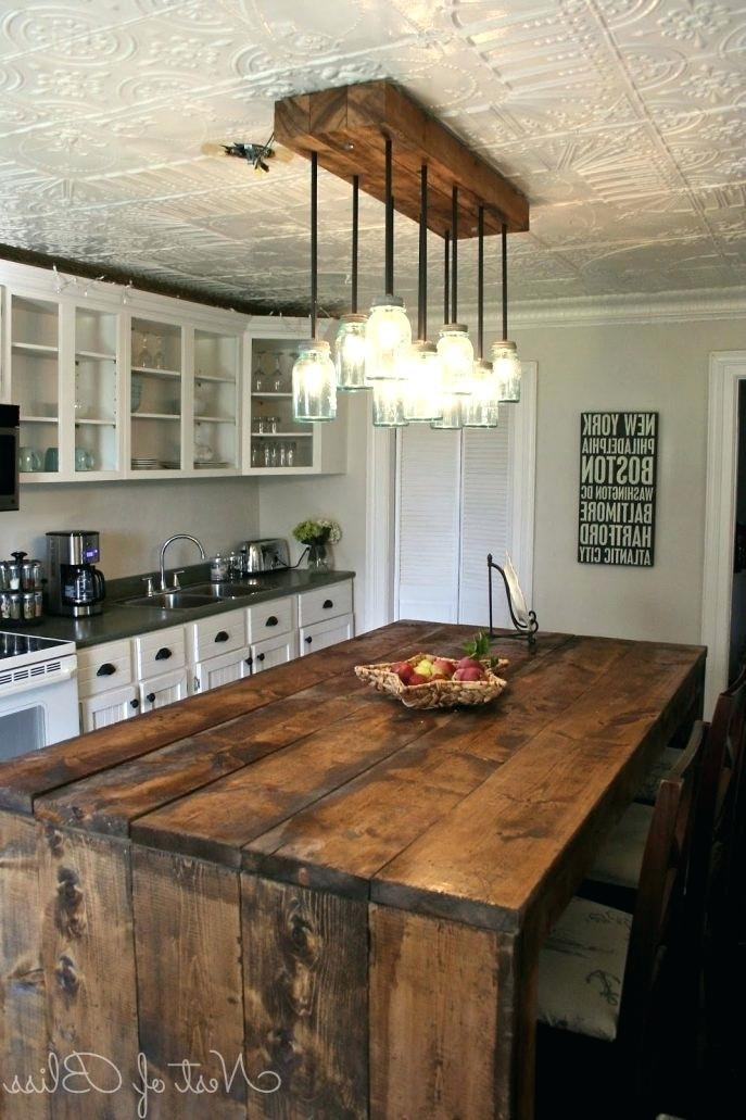Going with the farmhouse kitchen on a budget is fairly easy to do if you're good at DIY. This one features custom jar lighting with a custom dark stained wood island with seating that serves a dual purpose as a table.